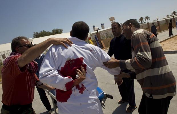 Integrante de equipe médica é socorrido após ser ferido em cidade próxima a Misrata nesta sexta-feira (29) (Foto: AP)