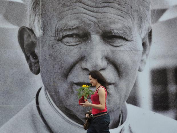 Fiel passa diante de imenso retrato do Papa João Paulo II na Cracóvia, Polônia, na quinta (28) (Foto: Bela Szandelszky / AP)
