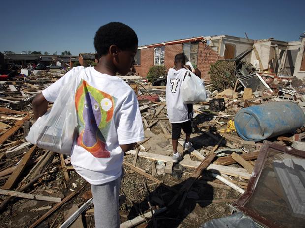 Em Rosedale, no Alabama, crianças procuram neste sábado (30) seus pertences em meio à destruição. (Foto: Reuters)