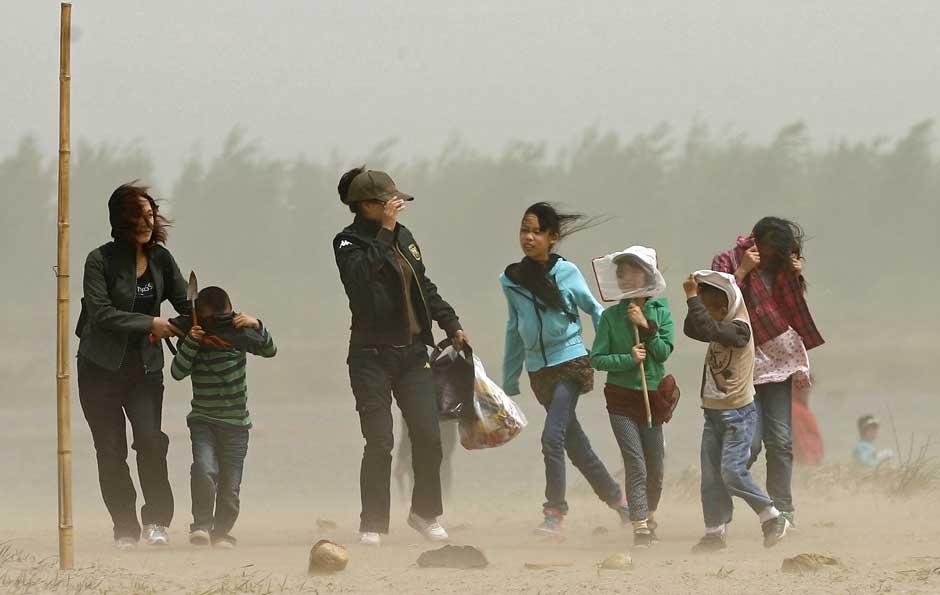 Uma tempestade de areia surpreendeu os chineses neste sábado (30), especialmente nos arredores de Shijiazhuang, província de Hebei, noroeste do país. Na imagem, grupo tem dificuldade para se locomover na região e uma criança usa uma rede para se proteger da poeira.   (Foto: Lee Pilar / Reuters)