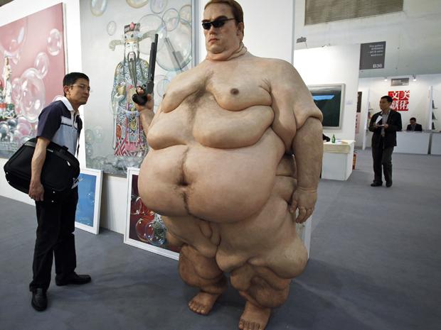 """A obra intitulada """"Arnold Schwarzenegger"""" foi destaque de uma feira de arte contemporânea inaugurada neste sábado (30), em Pequim, na China. A escultura do artista plástico Shu Yong mostra o governador da Califórnia numa versão nua e obesa e com os óculos e a arma de seu mais famoso personagem no cinema, o """"exterminador do futuro"""".  (Foto: AP) (Foto: AP)"""