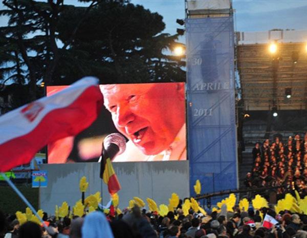 Peregrinos se reúnem em frente a uma tela que mostra imagens do Papa João Paulo II em Roma (Foto: Giuseppe Cacace/AFP)