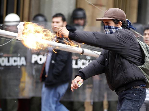 Manifestante dispara coquetel molotov contra a polícia no feriado de 1º de maio em Bogotá, Colômbia, neste domingo (1º) (Foto: AP)