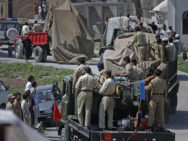 Soldados paquistaneses transporta nesta segunda (2) os destroços cobertos de um helicóptero, próximo ao local em que moradores reportaram combates em Abbotabad, no Paquistão. (Foto: Reuters)