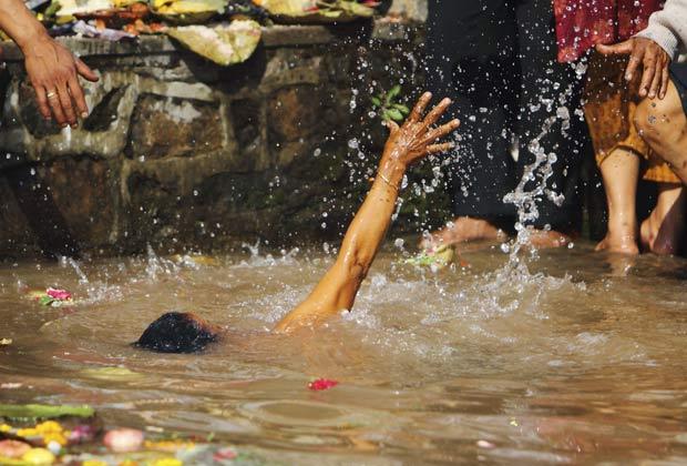 Mulher escorregou e caiu na água enquanto participava de ritual. (Foto: Navesh Chitrakar/Reuters)