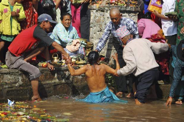 Mulher precisou ser socorrida para não se afogar. (Foto: Navesh Chitrakar/Reuters)