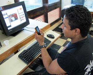 Robert Mendonça usa seu celular para escutar música enquanto acessa o Orkut (Foto: Laura Brentano/G1)