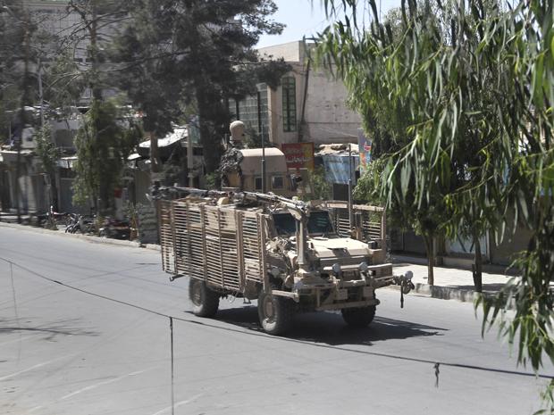 Veículo militar da Otan passa por rua deserta de Kandahar após o ataque deste sábado (7) (Foto: AP)