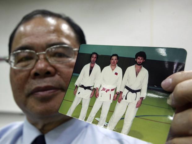 O treinador Jimmy Wu posa ao lado de uma das fotos do aluno que seria Osama bin Laden (Foto: Reuters)