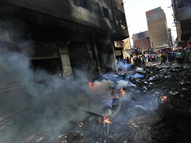 Moradores observam prédio pertencente a cristãos e que foi incendiado por muçulmanos neste domingo (8) em Imbaba, subúrbio do Cairo (Foto: AP)