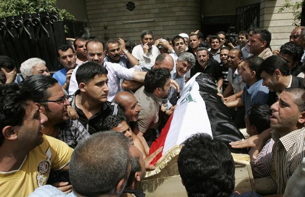 Corpo de policial morto durante a rebelião da véspera é enterrado neste domingo (8) em Bagdá (Foto: AP)