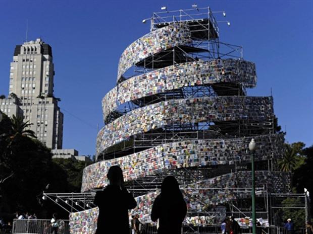 Casal tira fotos da 'Torre de Babel', uma criação feita pela artista argentina Marta Minujin com milhares de livros em línguas de todo o mundo, na praça San Martin, em Buenos Aires, neste sábado (7). A Organização das Nações Unidas para a Educação, a Ciência e a Cultura (Unesco) nomeou Buenos Aires como Capital Mundial do Livro 2011. (Foto: AFP/Mabromata Juan)