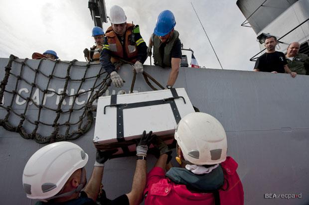 Foto tirada no sábado (7) e divulgada nesta segunda (9) mostra pessoas colocando no navio francês La Capricieuse uma caixa com o Flight Data Recorder (FDR), uma das caixas-pretas do Airbus A330 do voo 447 (Foto: AP/BEA)