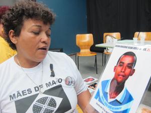 Débora Silva, presidente do movimento Mães de Maio, mostra foto do filho vítima dos ataques. (Foto: Caroline Hasselmann/G1)