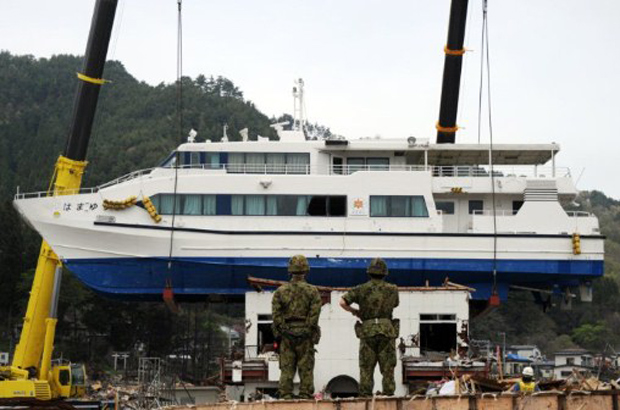 Militares japoneses observam guindaste que retira o barco Hamayuri do topo de prédio de dois andares nesta terça-feira (10) em Otsuchi, na prefeitura de Iwate. A embarcação foi parar sobre o edifício por conta do terremoto de magnitude 9 seguido de tsunami de 11 de março. (Foto: AFP)
