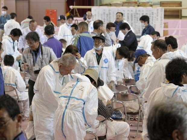92 moradores vestem roupas de proteção para uma breve visita às suas casas localizadas dentro da zona proibida da região da usina nuclear de Fukushima Dai-ichi. (Foto: Kyodo News / AP Photo)