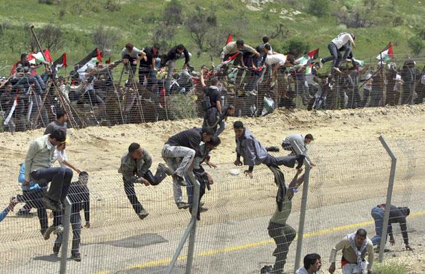 Manifestantes sírios cruzam a fronteira com Israel na região da vila druza de Majdal Shams, nas Colinas de Golã (Foto: Jalaa Marey/Reuters)