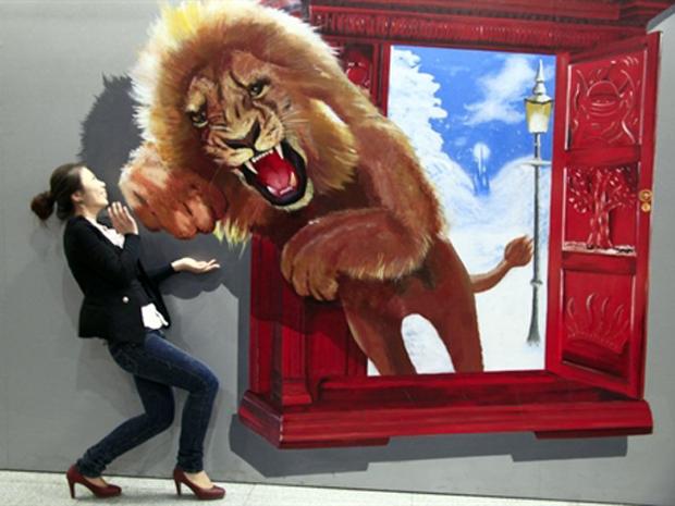 Mulher interage com pintura exposta em mostra de arte contemporânea na província chinesa de Jilin, no sábado (14), que mostra o salto de um leão. (Foto: AFP)