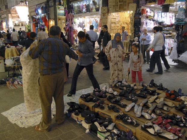 Moradores em mercado popular de Damasco, capital da Síria, nesta quarta-feira (18) (Foto: AP)