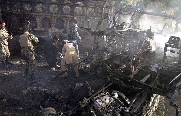 Afegãos tentam carregar vítima de ataque suicida a um ônibus da polícia em Jalalabad, na província de Nangarhar. Segundo autoridades, pelo menos 10 pessoas foram mortas (Foto: AP)