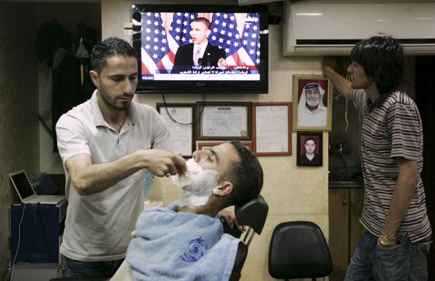 Palestinos assiste ao discurso de Obama nesta quinta-feira (19) em barbearia de Ramallah, na Cisjordânia (Foto: AP)
