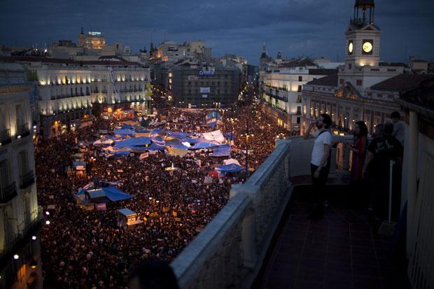 Milhares de pessoas ocupam a praça Puerta del Sol em Madri na noite desta sexta (20) (Foto: AP)