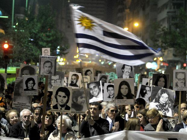 Manifestantes carregam cartazes com imagens de pessoas desaparecidas durante a ditadura uruguaia (Foto: Matilde Campodonico/AP)