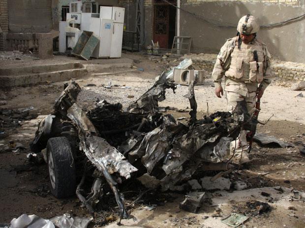 Soldado inspeciona os restos de um veículo usado em um ataque a bomba na cidade de Sadr, em Bagdá (Foto: Kareem Raheem/Reuters)