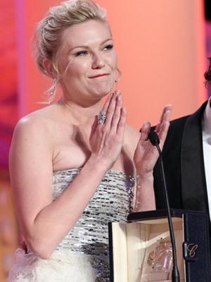 """Kirsten Dunst discursa em Cannes após receber o prêmio de melhor atriz por """"Melancolia"""", de Lars von Trier. (Foto: AFP)"""