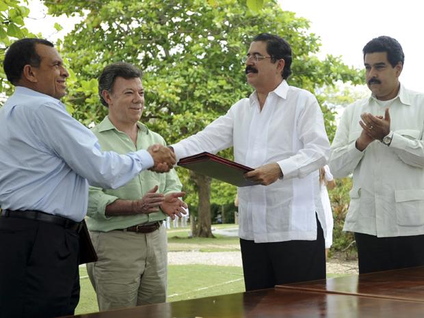 Presidente de Honduras Porfirio Lobo (E) dá a mão ao ex-presidente deposto,  Manuel Zelaya, depois de assinar um acordo para que ele possa voltar ao país (Foto: Reuters)