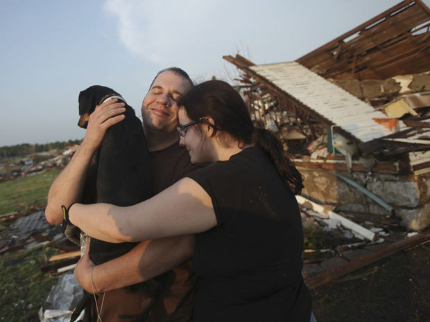 Trey Adams e Maggie Kelley abraçam seu cão, Saint, após achá-lo vivio entre os destroços de sua casa destruída por um tornado em Joplin, no estado americano do Missouri, nesta segunda-feira (23). O casal morava no local após ter perdido tudo na passagem d (Foto: AP)