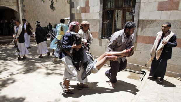 Membro de tribo ferido durante confronto com forças do governo é carregado por colegas nesta terça-feira (24) em Sanaa, capital do Iêmen (Foto: AP)