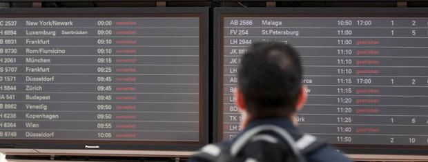 Passageiro observa painel em aeroporto de Hamburgo, no norte da Alemanha, nesta quarta-feira (25) (Foto: AP)