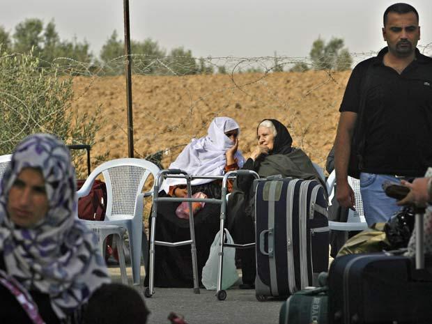Famílias palestinas, poucos antes da abertura da fronteira coma Faixa de Gaza. (Foto: Eyad Baba / AP Photo)