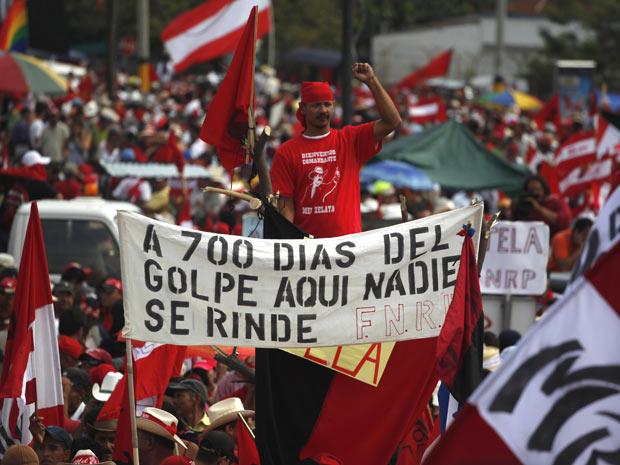 Multidão vestindo vermelho e levando faixas e cartazes aguarda a volta de Manuel Zelaya em Tegucigalpa neste sábado (28) (Foto: AP)