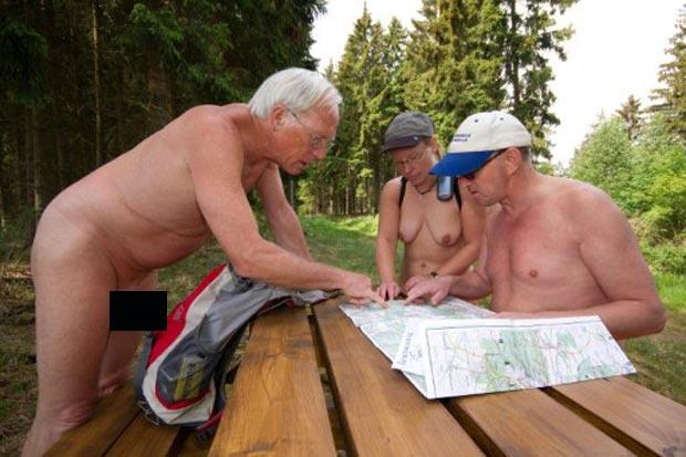 Na foto, três nudistas observam mapa durante caminhada na Alemanha. (Foto: Matthias Bein/AFP)