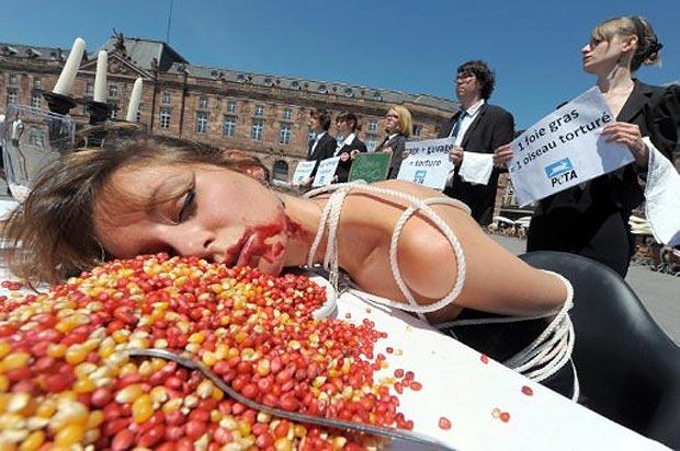 """Membro da associação Pessoas pelo Tratamento Ético de Animais (PETA, da sigla em inglês) simula cena de alimentação forçada enquanto manifestantes seguram cartazes com frases como 'gaiola + alimentação forçada = torturas' e 'um foie gras = uma ave torturada'. O protesto em Strasbourg, na França, foi contra a produção do 'fígado gordo' de pato ou ganso, o """"foie gras"""", uma das principais iguarias da culinária francesa. As aves precisam passar por um processo de superalimentação para a produção da iguaria. (Foto: AFP)"""