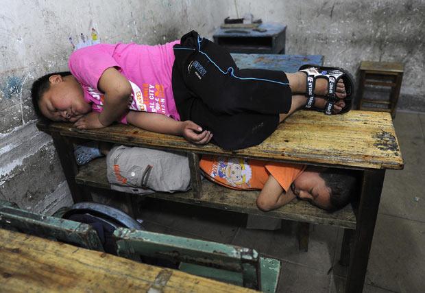 Dois meninos foram flagrados nesta quarta-feira (1) tirando uma soneca na sala de aula de uma escola primária em Hefei, província de Anhui, na China.  (Foto: Reuters)