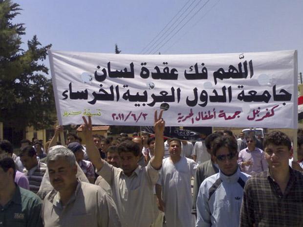 Manifestantes protestam contra o governo e pedem intervenção da Liga Árabe em marcha em Kfar-Nebel, norte da Síria, nesta sexta (3) (Foto: AP)