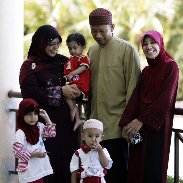 Ishak Md Nor, de 40 anos, segundo a partir da direita, com suas duas mulheres, Aishah Abdul Ghafar (à esq.), 40, e Afiratul Abidah Mohd Hanan, 25, e seus filhos no 'Clube da esposa obediente', em Kuala Lumpur, neste sábado (4) (Foto: AP)