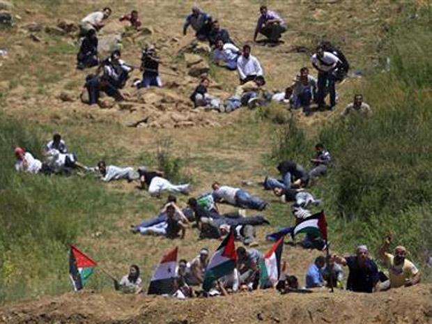 Manifestantes pró-palestinos protegem-se de disparos israelenses neste domingo (5) em Majdal Shams, nas colinas de Golan (Foto: AP)
