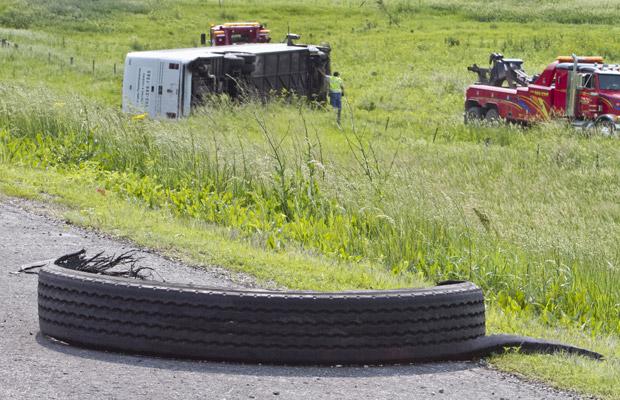 Ônibus que levava a banda marcial Casper Troopers é resgatado após rolar para fora da pista da Interestadual 80, próximo a Miden, no estado americano do Iowa. nesta segunda-feira (6). (Foto: AP)