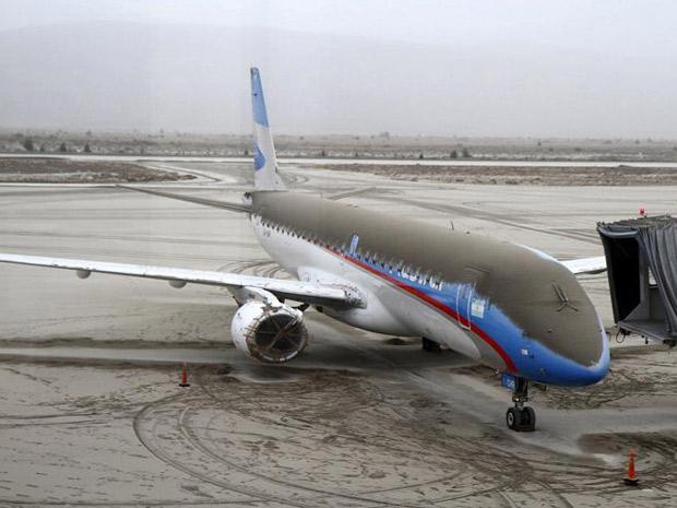 Avião da companhia aérea Austral coberto de cinzas do vulcão no aeroporto San Carlos de Bariloche, na Argentina (Foto: Chiwi Giambirtone / Reuters)