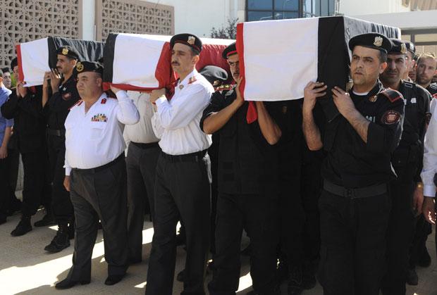 Imagem disponibilizada nesta terça (7) pela agência oficial Sana. Policiais sírios carregam caixões de colegas mortos durante os confrontos em Jisr al-Shughour, segundo informações da agência (Foto: AP/Sana)