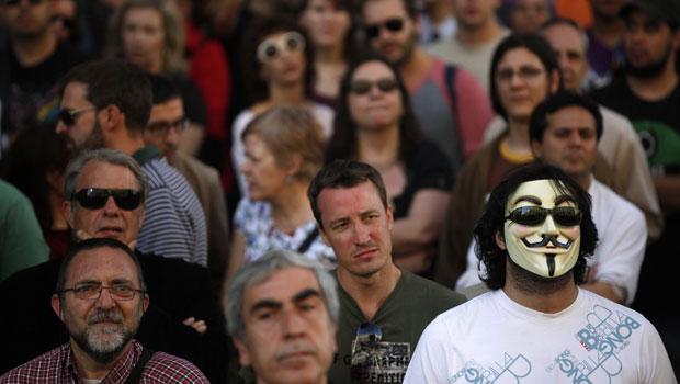 """Durante o movimento """"Democracia Real Agora"""", em Madri (Espanha), uma pessoa é vista com uma máscara do grupo de hackers Anonymous (Foto: Susana Vera/Reuters)"""