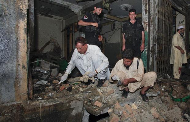 Oficiais fazem buscas em local atingido por bombas em Peshawar, no Paquistão (Foto: Fayaz Aziz/Reuters)