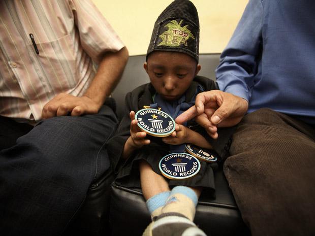Khagendra Thapa Magar, ex-homem mais baixo do mundo, olha nesta segunda-feira (13) para sua medalha do Livro Guinness de Recordes, enquanto esperava por audiência com o premiê do Nepal, Jhala Nath Khanal, em Katmandu. Ele entregou um documento ao premiê pedindo auxílio básico. Khagendra perdeu o título durante o fim de semana. (Foto: AP)