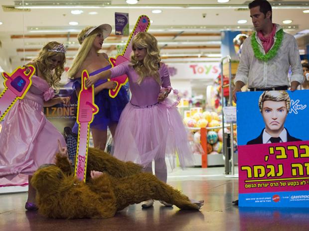 Em Israel, mulheres se vestiram como a boneca Barbie e com motosseras simulavam matar um animal. O Greenpeace quer alertar a Mattel contra o uso de madeira ilegal na produção de embalagens para a boneca Barbie (Foto: Reuters)