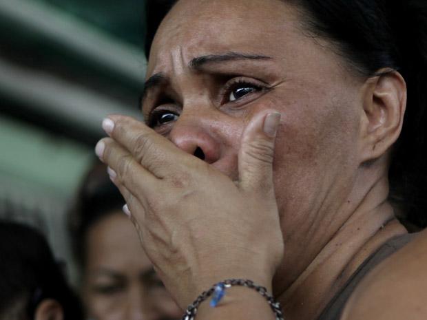 Parente espera por notícias de presos em frente à cadeia de El Rodeo nesta segunda-feira (13) (Foto: AP)
