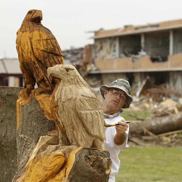 O professor de arte Paul Norris, da escola secundária de Joplin, impermeabiliza as águias que ele esculpou em árvore danificada pelo tornado que devastou a cidade americana no mês passado. A árvore ficava na frente da escola, cujo mascote é a águia. O objetivo é 'levantar o moral' da população, que ainda tenta recuperar os estragos provocados pelas tempestades (Foto: AP)